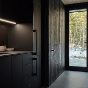 The kitchen continues the pared back black interior,