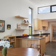 The kitchen features custom-design integrated shelving, incorporating ample
