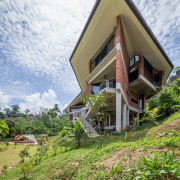 The house was designed to perch on the architecture, building, cottage, geological phenomenon, grass, home, house, land lot, property, real estate, residential area, roof, rural area, sky, tree, vacation, white, brown