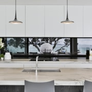 The black mirrored splashback allows the reflection of