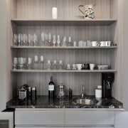 The bank of kitchen cabinetry includes a foldaway furniture, interior design, kitchen, shelving, gray