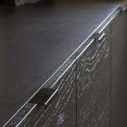 Minimalist pulls contribute to the kitchen's strong, minimalist