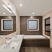 ​​​​​​​Natural tones and refined surfaces are features of architecture, bathroom, bathtub, building, ceiling, floor, furniture, home, house, interior design, plumbing fixture, property, real estate, room, sink, tap, tile, gray