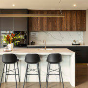 Marble-look tiles and wood veneer cabinetry create an
