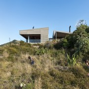The building design evolved from the idea of cottage, ecosystem, grass, hill, home, house, land lot, mountain, plant community, property, real estate, shrubland, sky, tree, brown, teal