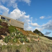 Studio2 Architects, designed this two-level beach house on architecture, cloud, cottage, grass, hill, home, house, land lot, landscape, mountain, property, real estate, rural area, sky, terrain, tree, teal, brown