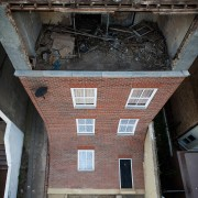 Alex Chinneck – From the knees of my architecture, beam, brick, brickwork, building, house, property, roof, wall, window, wood, black, gray