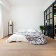Walls in the living room and bedroom are bed, bed frame, bedroom, floor, flooring, furniture, home, interior design, laminate flooring, mattress, room, wall, wood, wood flooring, gray, white