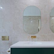 The dark green vanity is complemented by the