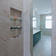 The new shower stall is seen in reflection.