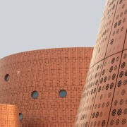 Tianjin Exploratorium's perforated facade up close. architecture, cylinder, font, text, red, white