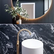 The Halo wall mirror reflects on the floor-mounted