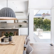 The wood dining table connects with the kitchen's