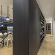 The kitchen had to provide separation between the architecture, building, ceiling, design, door, floor, flooring, furniture, glass, hall, house, interior design, loft, property, real estate, room, wall, gray, black