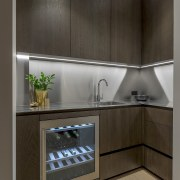 Room at the back – the dramatic, clean-lined building, cabinetry, countertop, cupboard, floor, flooring, furniture, gloss, interior design, kitchen, kitchen stove, material property, property, room, shelf, tile, black, gray