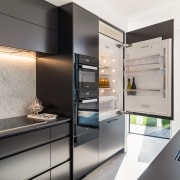 The sleek black handleless kitchen has top-of-the-line Miele apartment, architecture, building, cabinetry, ceiling, countertop, cupboard, design, floor, flooring, furniture, home, house, interior design, kitchen, material property, property, real estate, room, wall, white, gray