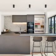 This modern kitchen's sleek and simple lines complement architecture, bar stool, building, cabinetry, ceiling, countertop, cuisine classique, cupboard, dining room, floor, flooring, furniture, home, house, interior design, kitchen, material property, property, real estate, room, table, white