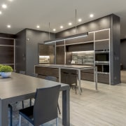 The kitchen cabinetry continues the aesthetic of the gray, black