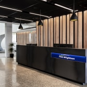 American beech panels behind the black reception desk