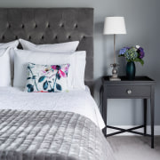 A padded headboard and elegant side table add