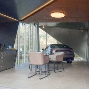 The one-car showroom space is equally sculptural on architecture, building, ceiling, daylighting, floor, furniture, house, interior design, property, roof, room, shade, wall, gray