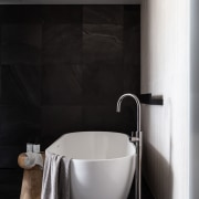 A freestanding bath with floor mounted pourer adds