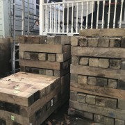 Just a few blocks to hold it up brick, brickwork, furniture, hardwood, lumber, room, wall, wood, black, gray