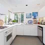 Before: the original kitchen in this reinvented home. building, cabinetry, ceiling, countertop, floor, furniture, home, house, interior design, kitchen, property, real estate, room, small appliance, white