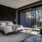 Floor-to-ceiling sliders open the master bedroom up up