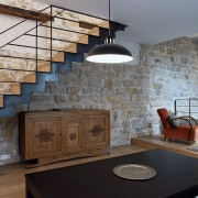 View of the living room and staircase from architecture, brick, building, ceiling, countertop, floor, flooring, furniture, hardwood, home, house, interior design, living room, loft, property, real estate, room, stairs, stone wall, table, wall, wood, gray