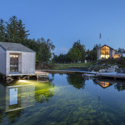 These holiday cabins form part of a wilderness architecture, bank, boathouse, building, calm, cottage, estate, home, house, inlet, lake, landscape, pond, reflecting pool, reflection, river, sky, tree, water, watercourse, waterway, teal, black