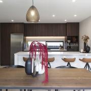 Dark wood cabinetry contrasts the crisp white island/breakfast