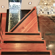 A glass tread on the stairs reveals water floor, flooring, handrail, hardwood, plywood, stairs, wood, wood flooring, wood stain, orange