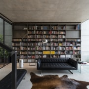 Floor-to-ceiling glazing ensures the home is light-filled and architecture, bookcase, building, ceiling, furniture, home, house, interior design, library, living room, loft, room, shelf, shelving, gray, black