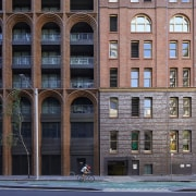 At street level, the mixed-use residential building melds apartment, arch, architecture, building, city, classical architecture, commercial building, condominium, downtown, facade, human settlement, landmark, metropolis, metropolitan area, mixed-use, neighbourhood, real estate, urban area, black, gray