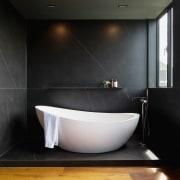 The freestanding bath sits on a pedestal floor