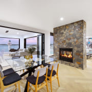The central feature fire can also heat the apartment, architecture, building, ceiling, design, dining room, estate, fireplace, floor, flooring, furniture, hearth, home, house, interior design, living room, property, real estate, room, table, wall, white