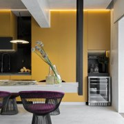 The mustard coloured cabinetry, set in contrast to architecture, building, cabinetry, ceiling, countertop, floor, furniture, home, house, interior design, kitchen, living room, material property, property, purple, real estate, room, table, violet, yellow