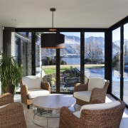 Wicker chairs and a circular table have an estate, home, interior design, living room, property, real estate, window, gray