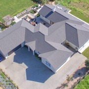 ​​​​​​​This U-shaped Fowler Homes residence wraps around three aerial photography, architecture, bird's eye view, estate, home, house, property, real estate, roof, gray, fowler homes, new home,  house, design and build