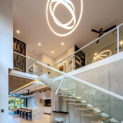 A dramatic pendant draws attention to the scale apartment, architecture, ceiling, daylighting, handrail, home, house, interior design, lobby, stairs, gray