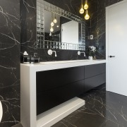 The geometric shape of the vanity in this bathroom, cabinetry, countertop, floor, flooring, furniture, interior design, room, tile, wall, black