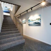 ​​​​​​​Ocean-themed artworks add to the coast feel in architecture, floor, flooring, carpet, home, house, interior design, stairs, carpet