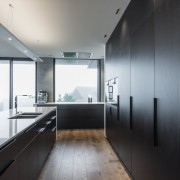 ​​​​​​​Understated cabinetry handles contribute to the pared-back look architecture, countertop, daylighting, house, interior design, kitchen, gray, black