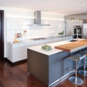 This entertainer's kitchen by Kitchen Distributors includes a cabinetry, countertop, interior design, kitchen, white, timber floor,