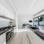 ​​​​​​​The long, clean lines of this kitchen match architecture, countertop, benchtop, Ceasarstone, kitchen, white cabinetry, Island, appliances, Emma Morris, Eterno Design