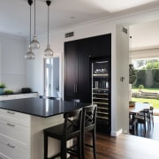 ​​​​​​​In this heart-of-the-home kitchen, the tall black pantry countertop, classique, interior design, kitchen, cabinetry, black, white, Caesarstone, wine fridge, vintec, IL Design,