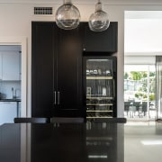 ​​​​​​​In this kitchen by IL Design, the tall home appliance, interior design, kitchen, white, black, IL Design, Caesarstone, wine fridge, vintec,
