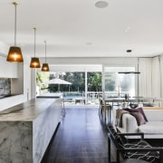 ​​​​​​​The stone-clad island, perimeter benchtop and splashback have house, interior design, living room, villa, timber floor, stone island, kitchen, Matt Brew Architect