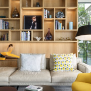 This family living area in front of the bookcase, couch, furniture, home, interior design, living room, room, shelf, shelving, table, wall, white, SAOTA